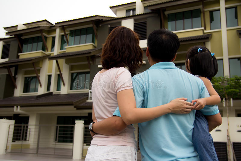Family with dream house. Couple with a kid in front of a house in modern residential area