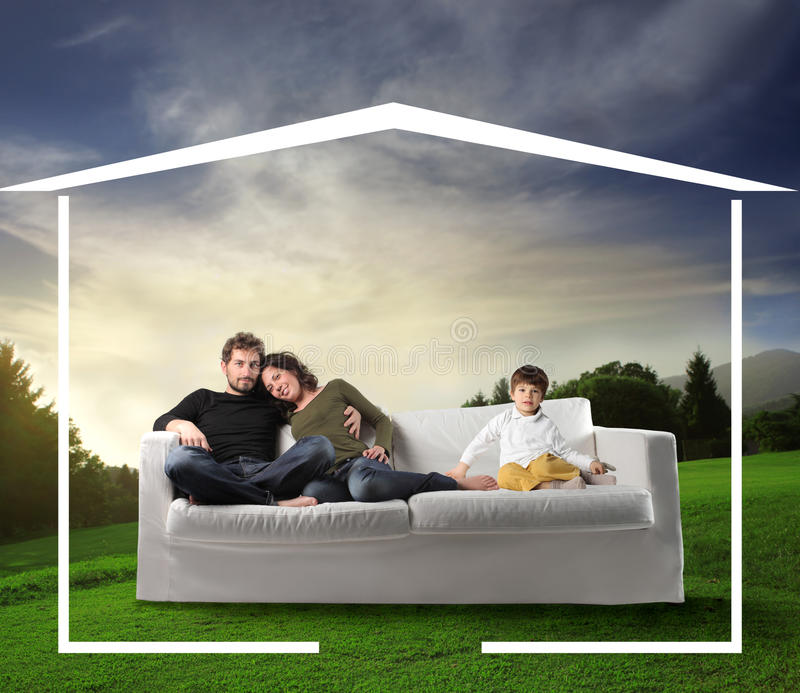 Family dreaming a home. Young family seated on a sofa in the nature and home drawing around them