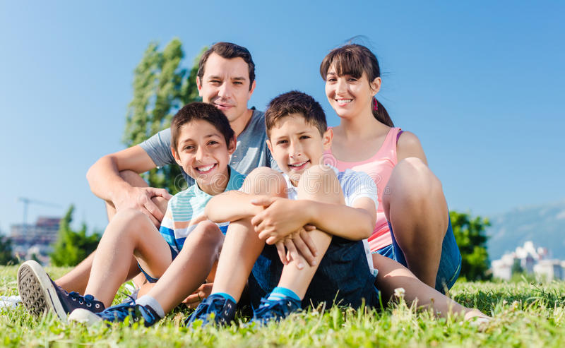 Family dressed in white in park in summer sitting in meadow stock photos