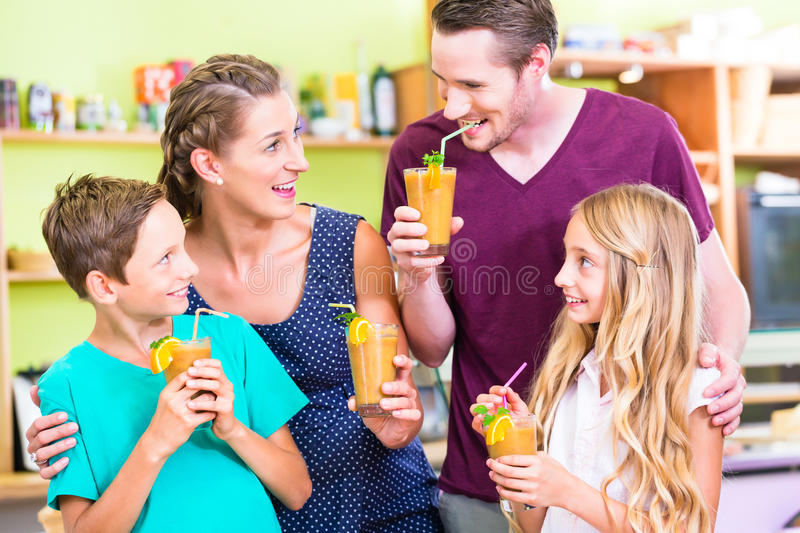 Family drinking smoothie or juice in domestic kitchen. Parents and children drinking smoothie or juice in domestic kitchen royalty free stock images