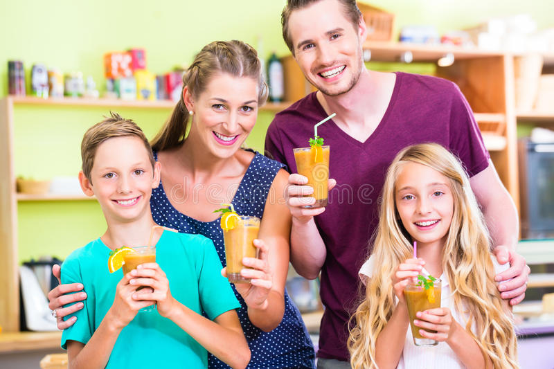 Family drinking smoothie or juice in domestic kitchen. Parents and children drinking smoothie or juice in domestic kitchen stock image