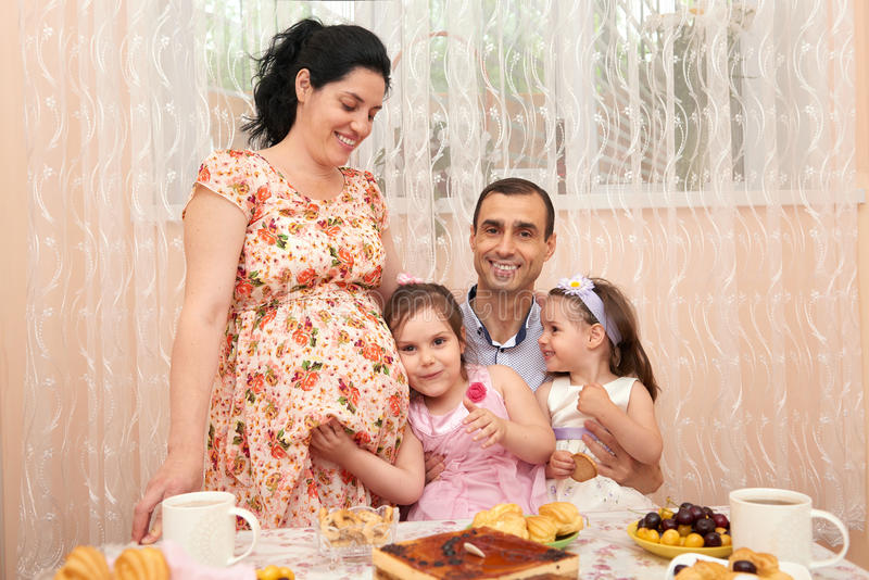Family drinking tea in dining room, pregnant woman royalty free stock photo