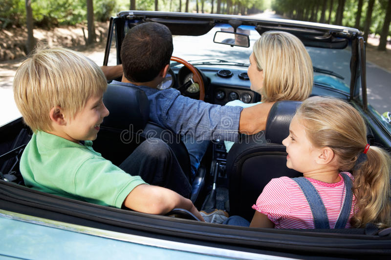 Family driving in sports car stock photography