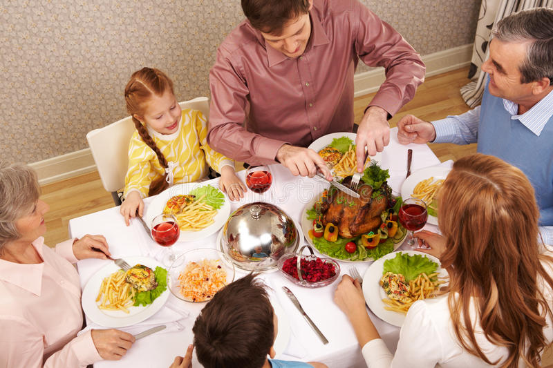 Family eating. Image of big family sitting at festive table and eating salad and roasted turkey royalty free stock photo
