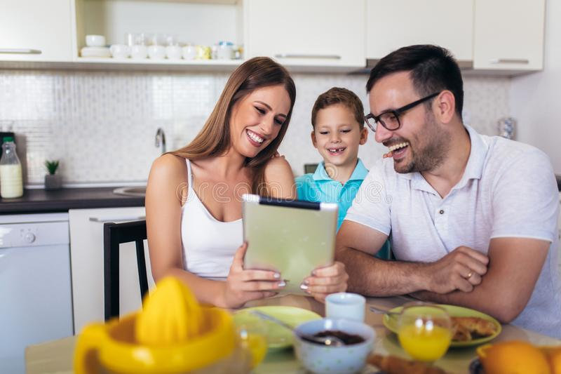 Family eating breakfast at kitchen table using digital tablet. Young family eating breakfast at kitchen table using digital tablet stock images