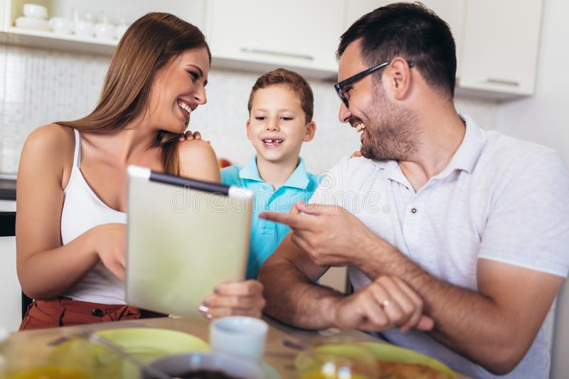 Family eating breakfast at kitchen table using digital tablet. Young family eating breakfast at kitchen table using digital tablet stock photography