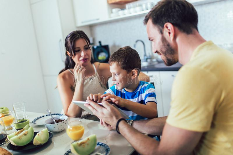 Family eating breakfast at kitchen table and using digital tablet. Having fun royalty free stock photography