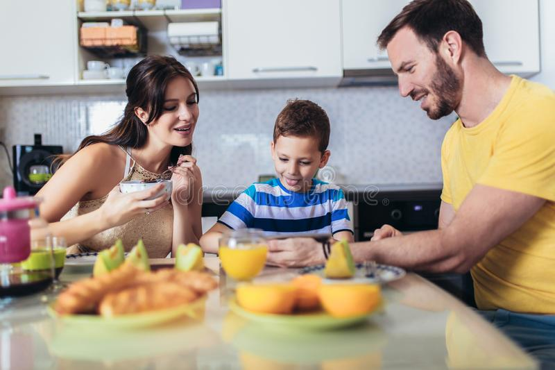 Family eating breakfast at kitchen table and using digital tablet. Having fun royalty free stock image