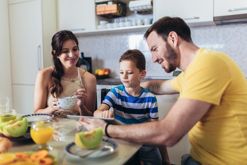 Family eating breakfast at kitchen table and using digital tablet. Having fun stock images