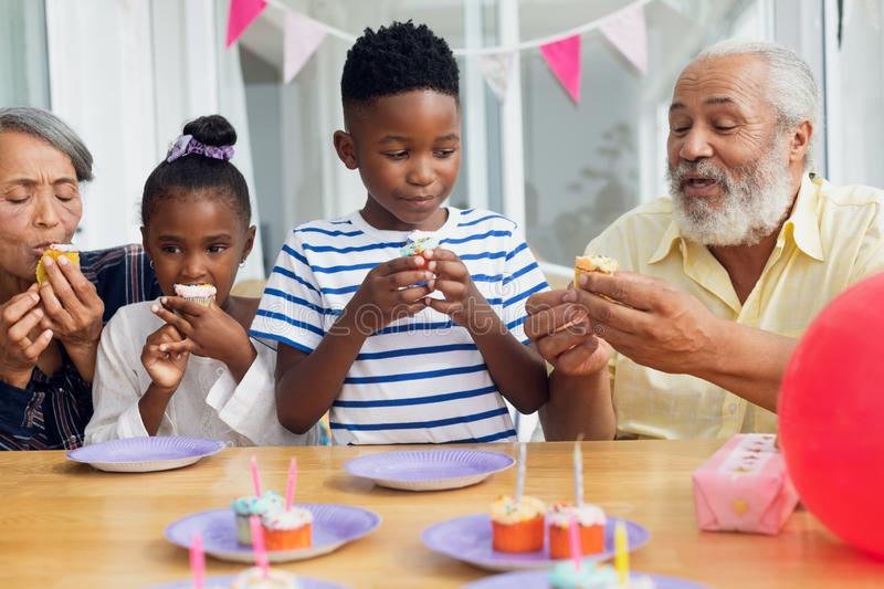 Family eating cupcakes stock photography