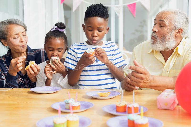 Family eating cupcakes. Front view of African-American family eating cupcakes. Authentic Senior Retired Life Concept royalty free stock images