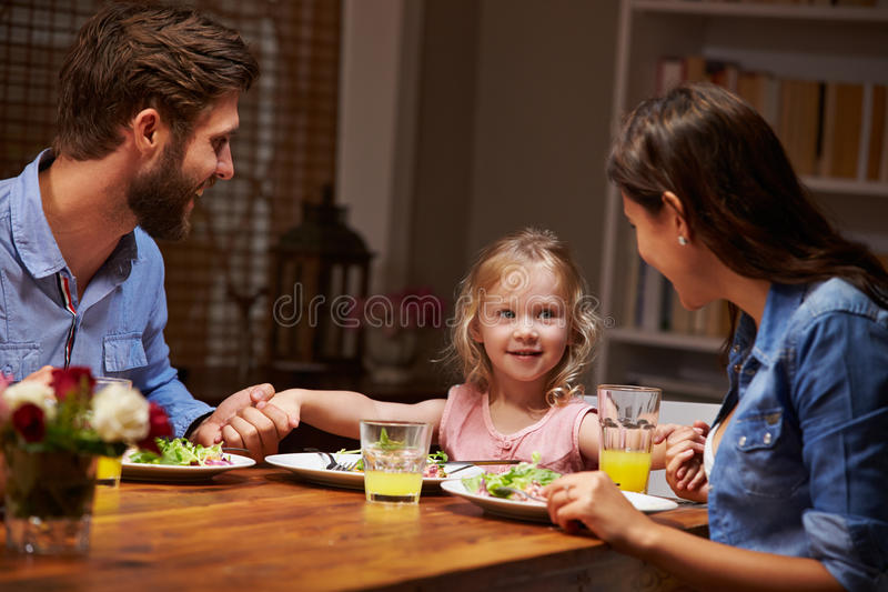 Family eating dinner at a dining table royalty free stock photos