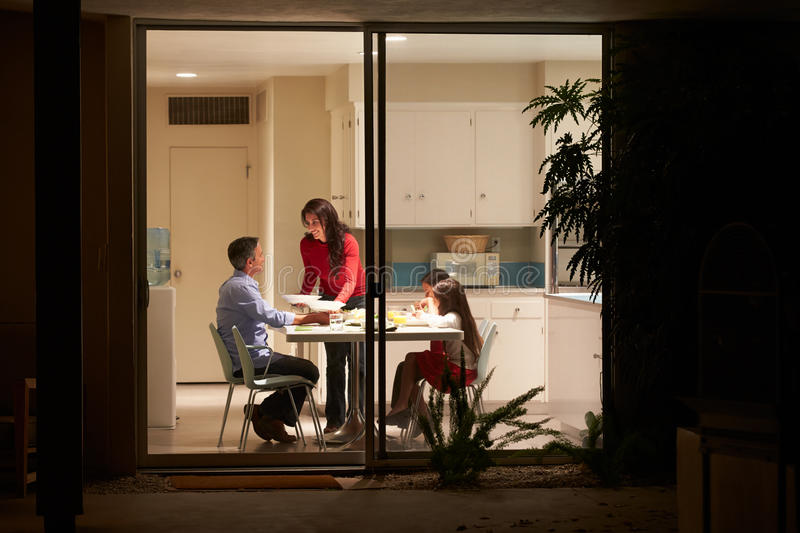 Family Eating Evening Meal Viewed From Outside. Family Eating Evening Meal Sitting At Table Viewed From Outside stock photo