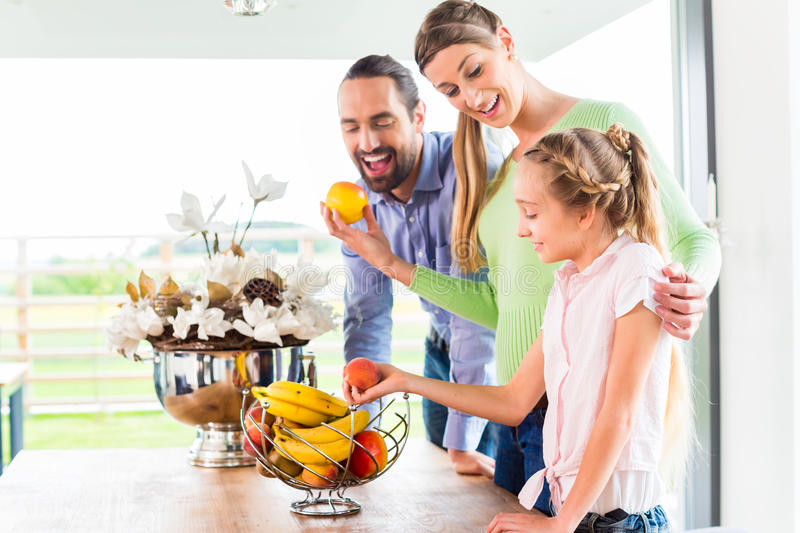 Family eating fresh fruits for healthy living in kitchen. Mother, father, child picking fresh fruits for healthy living in home kitchen royalty free stock image