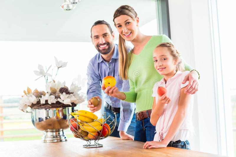 Family eating fresh fruits for healthy living in kitchen. Mother, father, child picking fresh fruits for healthy living in home kitchen royalty free stock photos