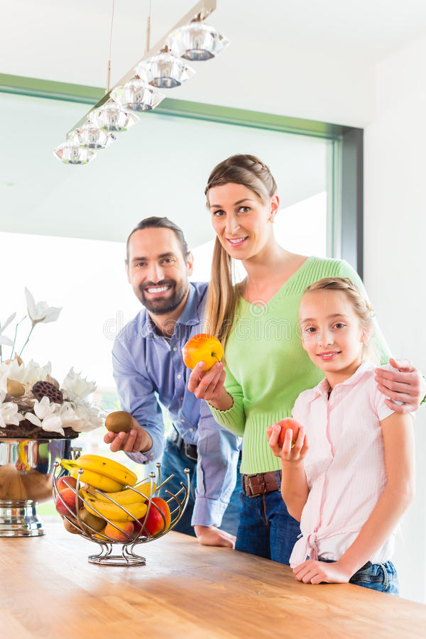 Family eating fresh fruits for healthy living in kitchen. Mother, father, child picking fresh fruits for healthy living in home kitchen royalty free stock photo