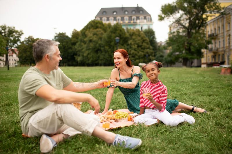Family eating fruits and drinking juice while having picnic. Family drinking juice. Family eating fruits and drinking juice while having picnic in the park royalty free stock photography