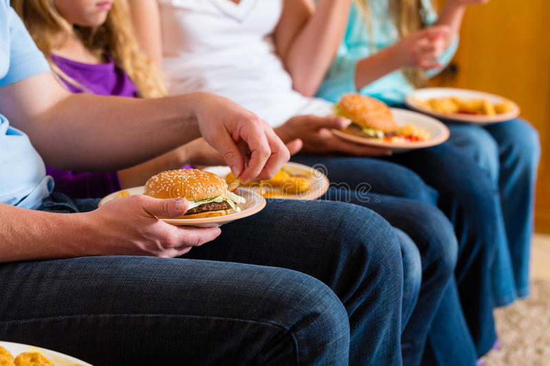 Family is eating hamburger or fast food. Young family - mother, father and daughters - is eating hamburger or fast food at home royalty free stock image