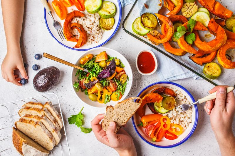 Family eating a healthy vegetarian food. Vegan lunch table top view, plant based diet. Baked vegetables, fresh salad, berries,. Flat lay of family hands eating stock images