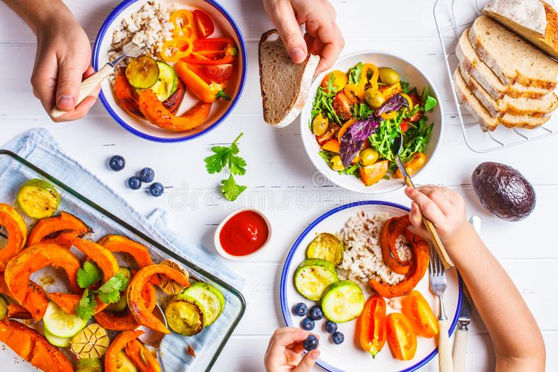 Family eating a healthy vegetarian food. Vegan lunch table top view, plant based diet. Baked vegetables, fresh salad, berries,. Flat lay of family hands eating royalty free stock photo