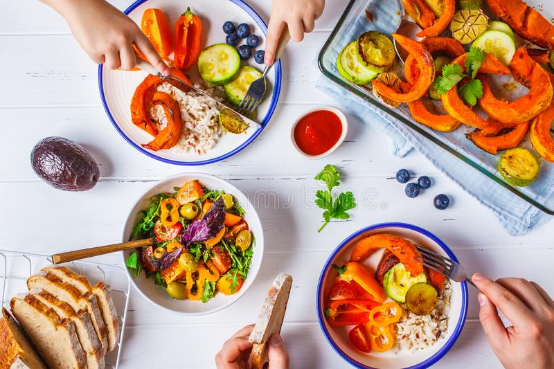 Family eating a healthy vegetarian food. Vegan lunch table top view, plant based diet. Baked vegetables, fresh salad, berries,. Flat lay of family hands eating stock photo