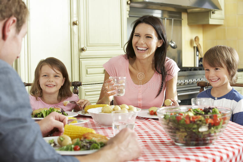 Family Eating Meal Together In Kitchen stock photo