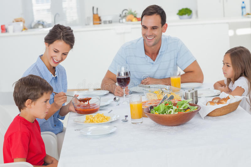 Family eating pasta and salad. In the dining room stock photography