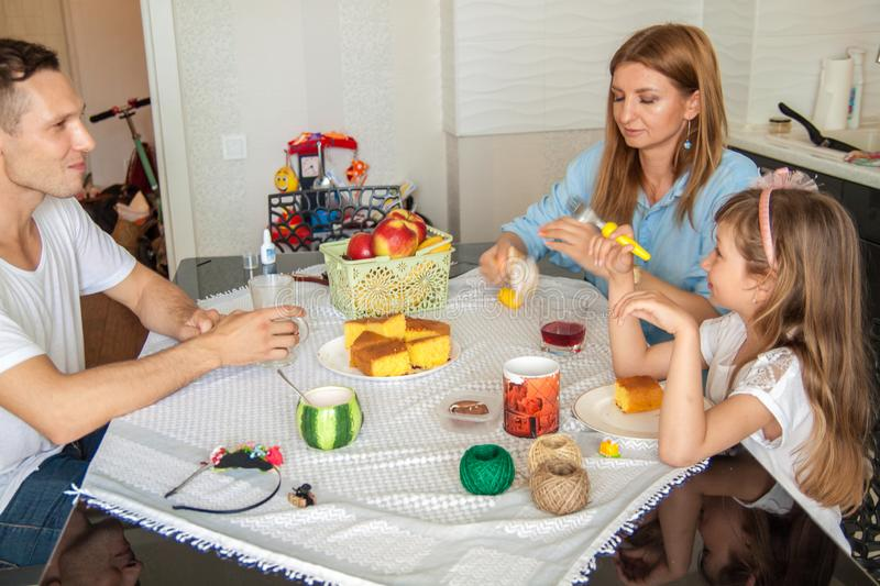 Family, eating and people concept - happy mother, father and daughter having breakfast at home. royalty free stock image
