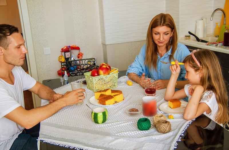 Family, eating and people concept - happy mother, father and daughter having breakfast at home. stock images