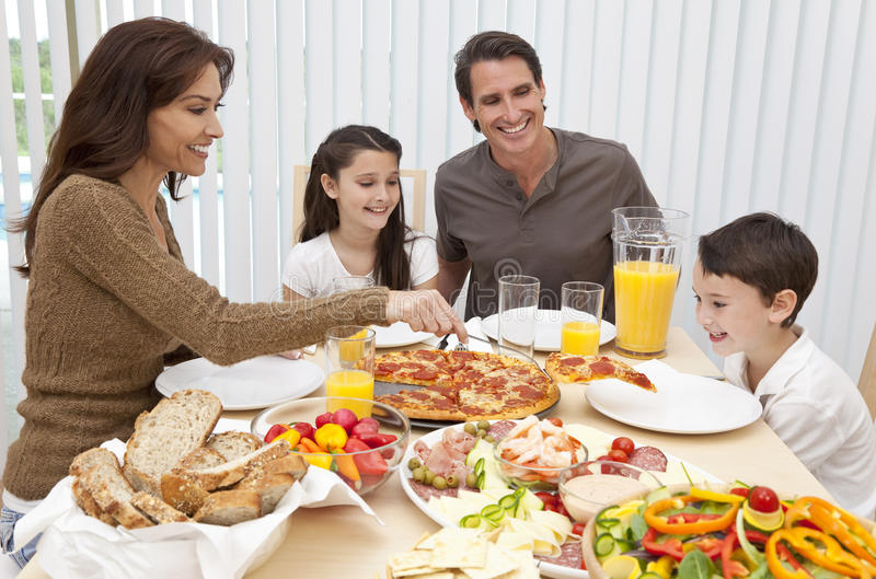 Family Eating Pizza & Salad At Dining Table Royalty Free Stock Image