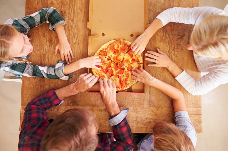 Family eating pizza together, overhead view royalty free stock photo
