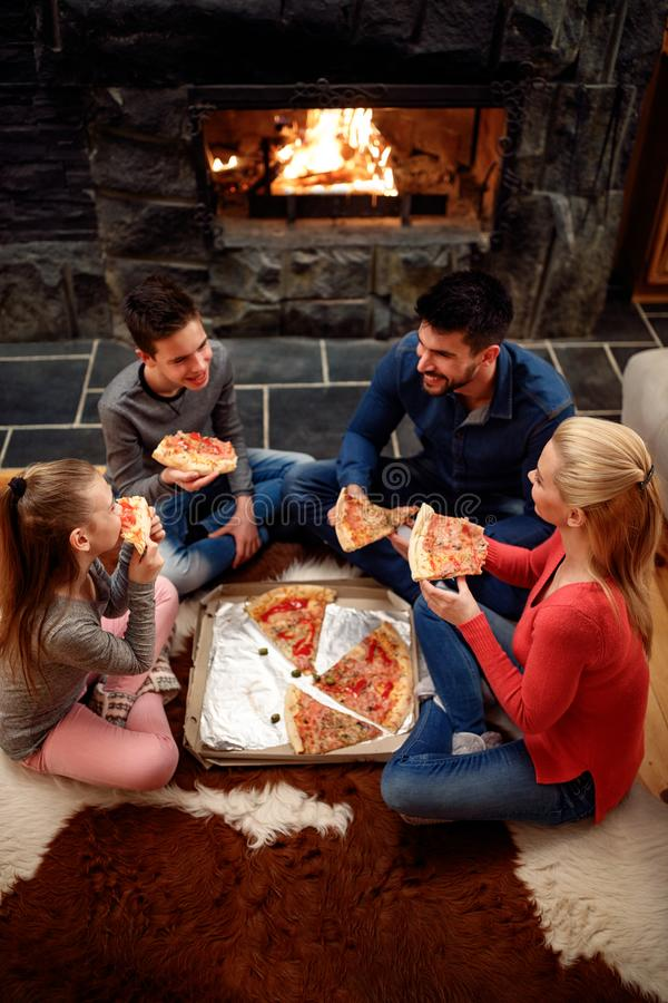 Family eating pizza together, overhead view stock photo