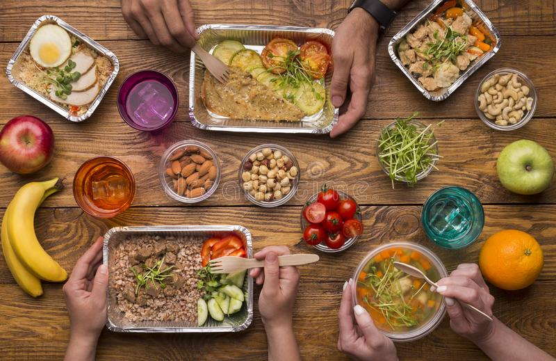 Family eating from take away boxes on wooden table stock image
