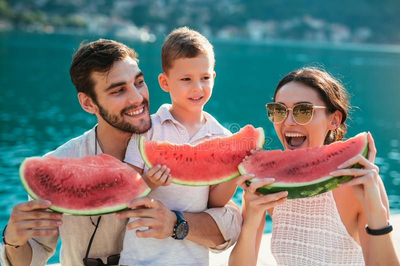 Family eating watermelon. Little boy and his parents on the sea shore having fun. Joyful family on the seaside royalty free stock photography