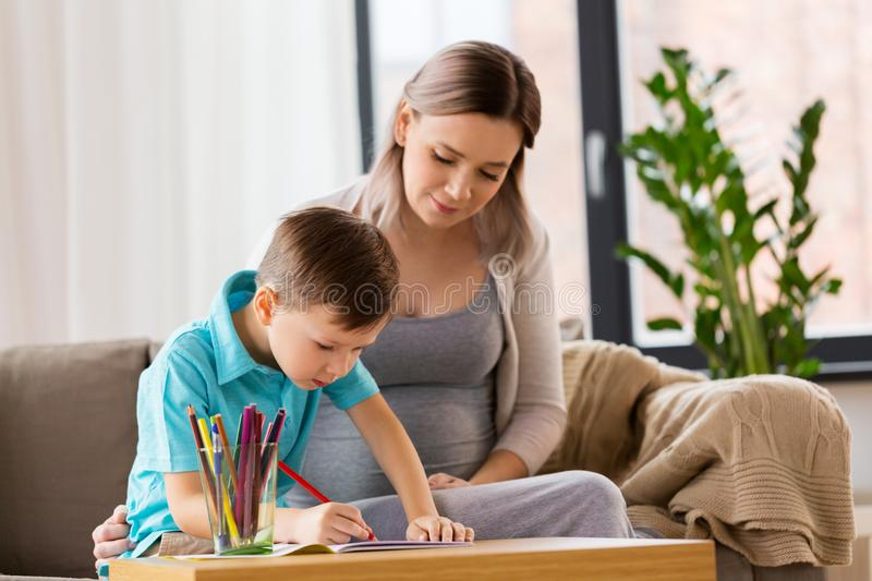 Pregnant mother and son with workbook at home. Family, education and pregnancy concept - happy pregnant mother and little son with workbook writing or drawing at stock images