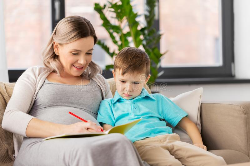 Pregnant mother with workbook and son at home. Family, education and pregnancy concept - happy pregnant mother with little son writing or drawing in workbook at stock images