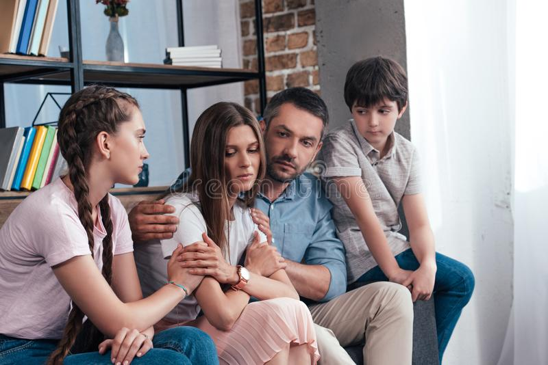 Family embracing and cheering up frustrated woman. Family embracing and cheering up frustrated women on sofa in counselor office royalty free stock photos