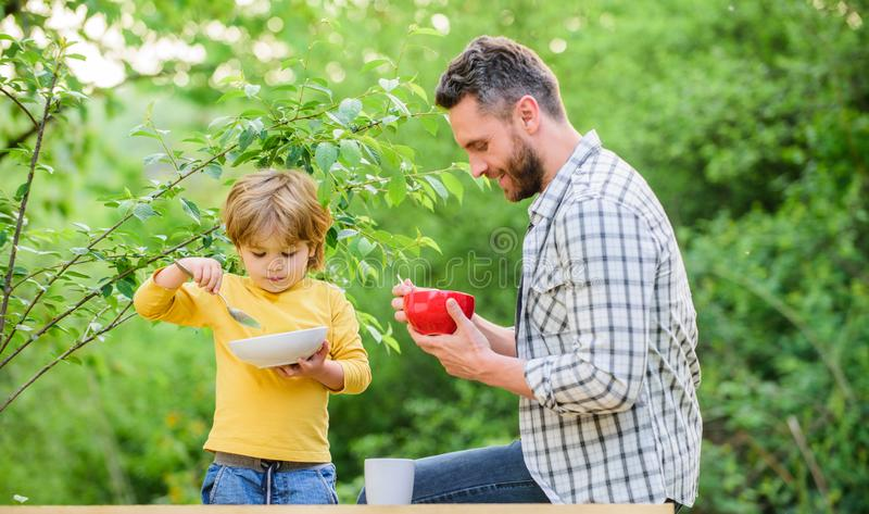 Family enjoy homemade meal. Healthy breakfast. Father son eat food. Little boy and dad eat. Nutrition kids and adults. Tasty porridge. Organic nutrition royalty free stock image