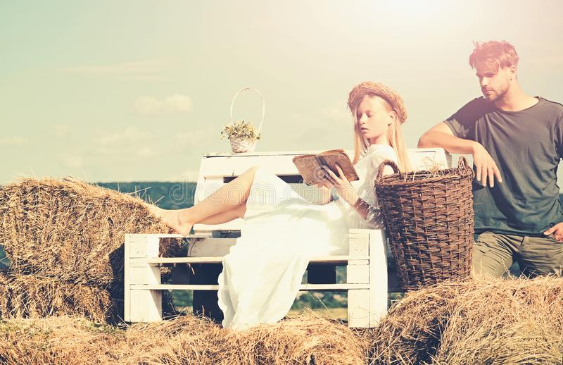Family enjoy summer nature. Woman bride in wedding dress relax on bench. Sensual woman read book for man. Couple in love. Family enjoy summer nature. Woman bride stock image