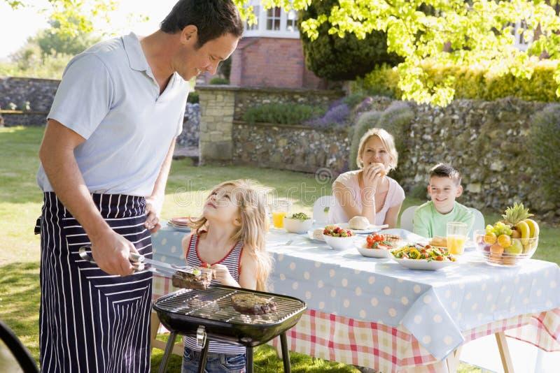 Family Enjoying A Barbeque. Smiling stock photos