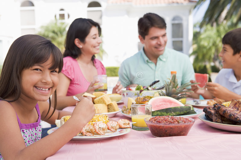 Family Enjoying A Barbeque. A Family Enjoying A Barbeque royalty free stock image