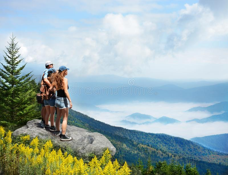 Family enjoying beautiful view of foggy mountains. Family hiking on vacation. Father standing with arms around his family on top of mountain, over clouds royalty free stock photography