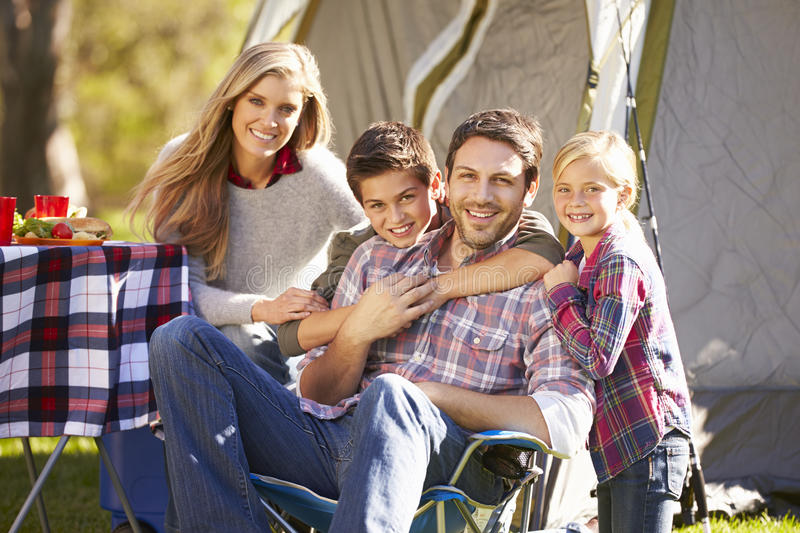 Family Enjoying Camping Holiday In Countryside. Smiling To Camera royalty free stock images