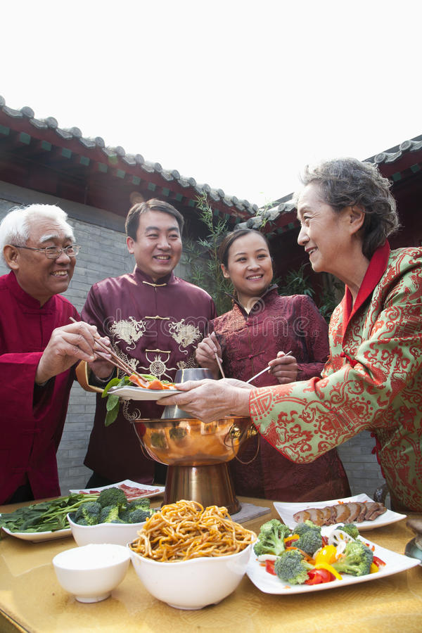 Family enjoying Chinese meal in traditional Chinese clothing royalty free stock images