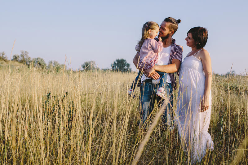 Family enjoying life outdoors in field. Father holds the little daughter with them standing a pregnant mother. Family enjoying life outdoors in field royalty free stock photo