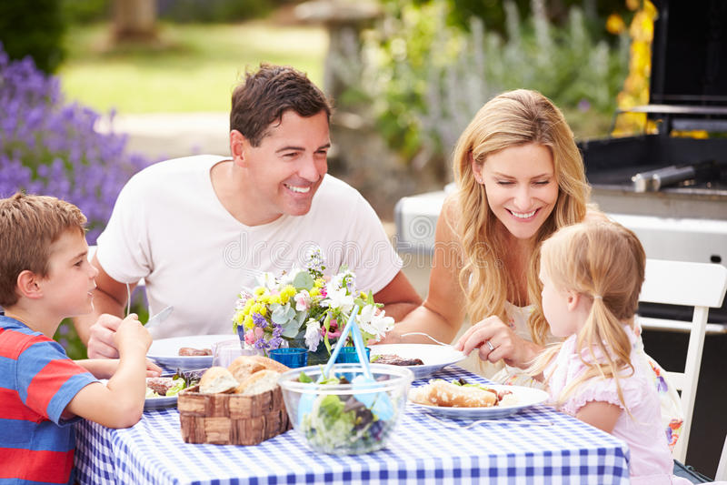 Family Enjoying Outdoor Meal In Garden stock image