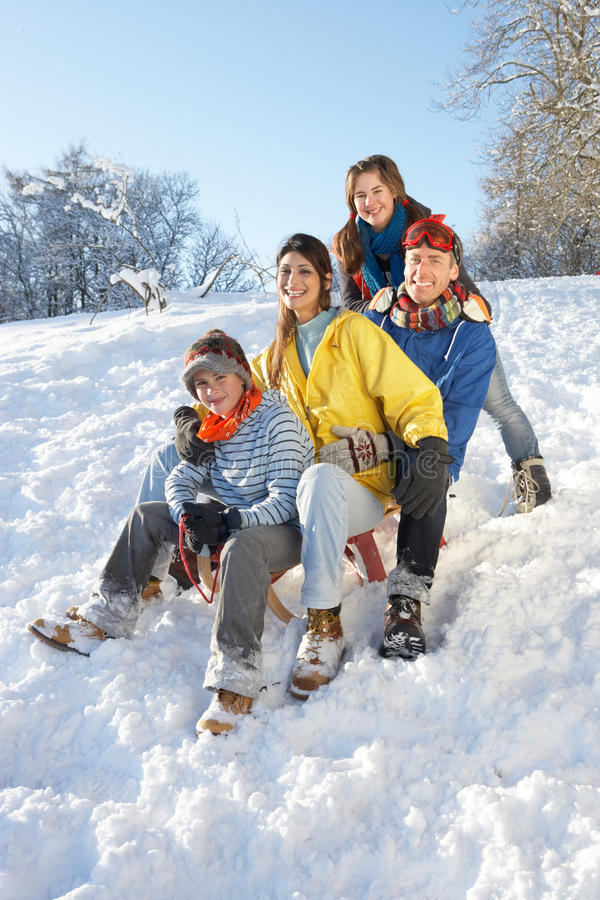 Free Family Enjoying Sledging Down Snowy Hill Royalty Free Stock Image - 14189056