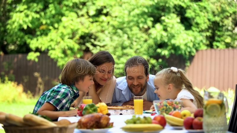 Family enjoying smell of fragrant pizza, italian cuisine, food delivery service stock images