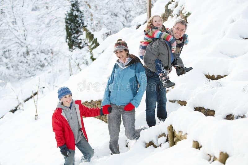 Family Enjoying Walk Through Snowy Landscape royalty free stock photo