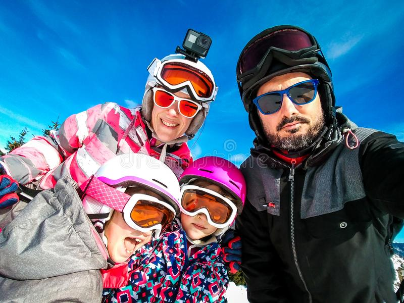 Family enjoying winter vacations taking selfie in skiing gear stock images